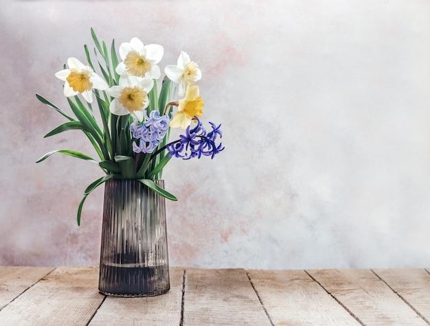 Lente boeket van gele narcis en blauwe en paarse hyacint in glazen vaas op rustieke houten oppervlak