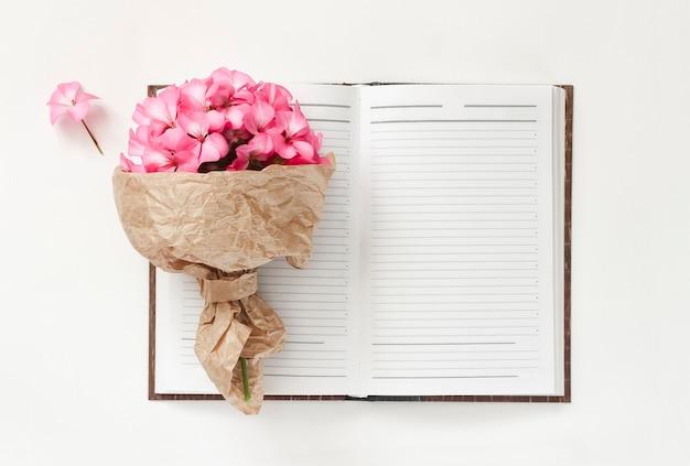 Lente boeket van roze bloemen in kraft inpakpapier met notitieboekje