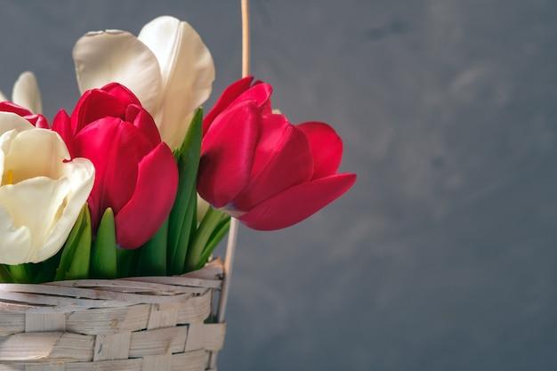 Lente boeket van tulpen in mand op vintage achtergrond.
