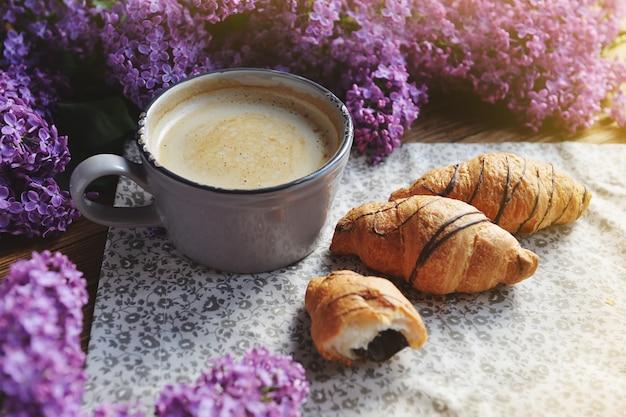Lente cet en vers ontbijt op een houten tafel. op tafel staan serene croissants en een cappuccino-kop. een boeket van lila op een houten tafel.