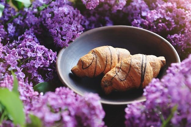 Lente cet en vers ontbijt op een houten tafel. siren croissants zijn op tafel. een boeket van lila op een houten tafel.