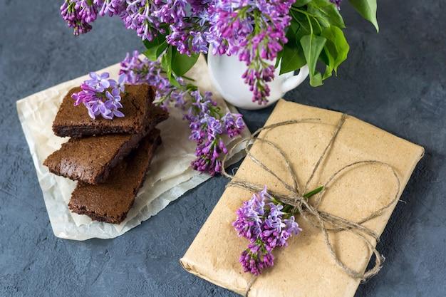 Lente compositie met geschenkdoos, lila bloemen en brownie, natte cake. dessert voor geserveerd voor thee of koffiepauze in houten kist. snack op een lentedag in de tuin.