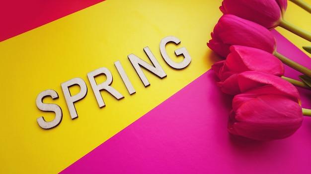 Lente concept. boeket tulpen op kleurrijke achtergrond. moederdag of 8 maart feestelijk thema. close-up met tekst lente. lente verkoop banner