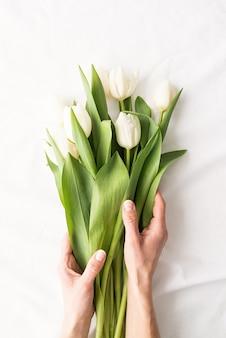Lente concept. bovenaanzicht die van vrouwenhanden wit tulpenboeket op witte stoffenachtergrond houden
