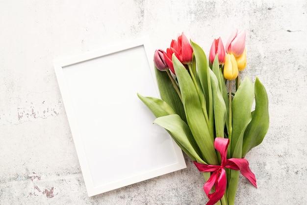 Lente concept. kleurrijk tulpenboeket en leeg kader op witte achtergrond met exemplaarruimte