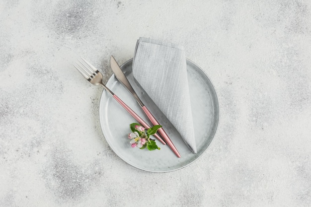 Lente couvert met bloeiende appelboomtakken en bloemen op lichttafel. vakantiedecoratie in provençaalse stijl. romantisch diner. overhead met kopieerruimte voor tekst