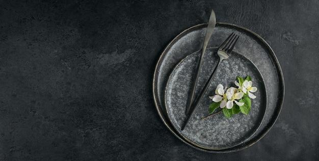 Lente couvert tafel instelling met bloeiende appelboom takken en bloemen op zwarte tafel. vakantiedecoratie in provençaalse stijl. romantisch diner. overhead met kopieerruimte voor tekst