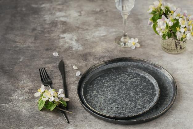Lente couvert tafel met bloeiende appelboomtakken en bloemen op grijze tafel. vakantiedecoratie in provençaalse stijl. romantisch diner. overhead met kopieerruimte voor tekst