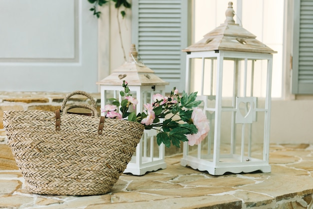 Lente decoraties. rieten mand met bloemen en kandelaars op de veranda van het huis