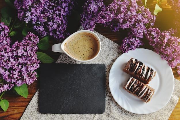 Lente en vers ontbijt op een houten tafel. op tafel staan seringen, cakes en een cappuccino. een boeket van lila op een houten tafel.