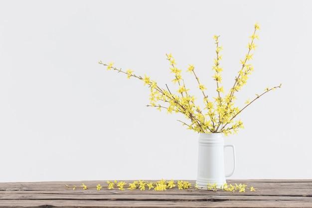 Lente gele bloemen in witte kruik op wit oppervlak