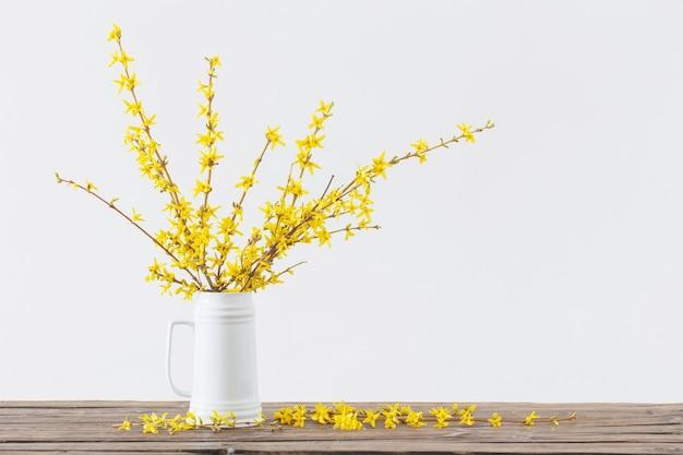 Lente gele bloemen in witte kruik op witte achtergrond