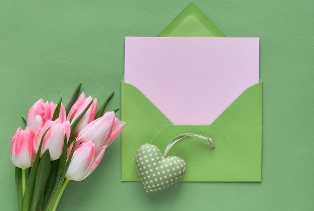 Lente groene achtergrond met roze tulpen, hyacint, ingepakte geschenkdozen en decoratief gevuld hart met stippen