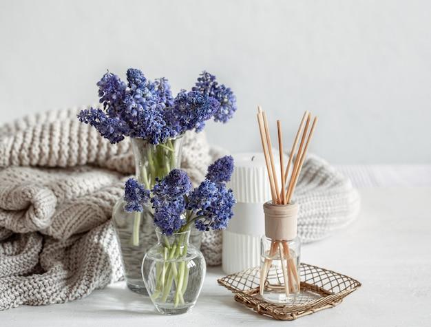 Lente huis compositie met bloemen, aroma sticks en gebreid element.