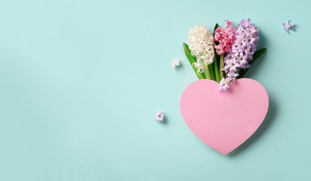Lente hyacint bloemen en roze papieren hart.