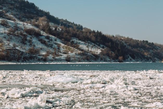 Lente-ijs dat op de rivier drijft