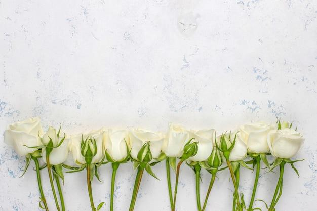 Lente kaart met witte rozen en bloemen, bovenaanzicht