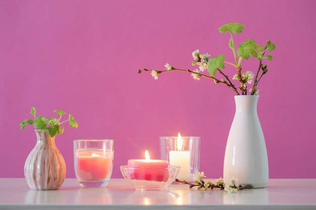 Lente kersen bloemen en kaarsen op roze achtergrond
