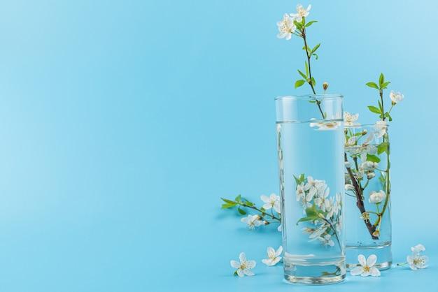 Lente kersenbloeiende bloemen en vervormde bloemen door waterglas op blauwe ondergrond