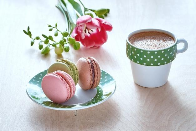 Lente koffie. roze tulp, fresia, espresso en macarons met lentebloemen