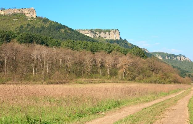 Lente krim berglandschap en landelijke wegen in de vallei (mangup boerenkool - historisch fort en oude grot nederzetting in de krim, oekraïne)