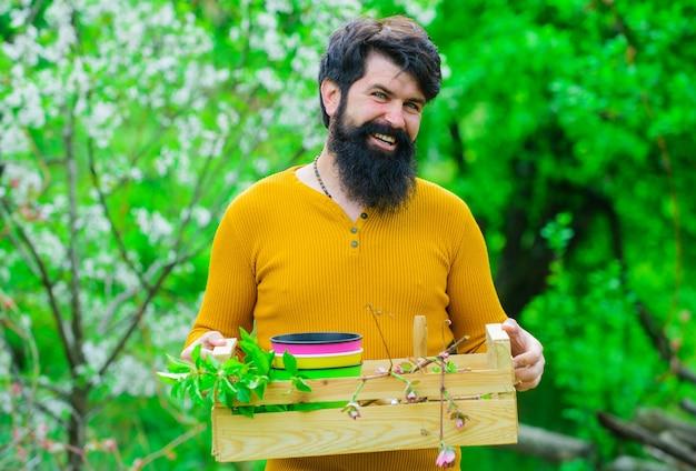 Lente landbouw, boer met doos, bebaarde man bereidt zich voor op planten.