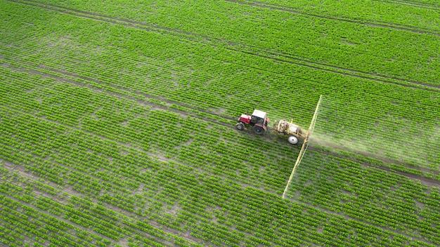 Lente landbouwwerk in de velden. de tractor bespuit gewassen met herbiciden, insecticiden en pesticiden.
