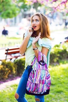 Lente levensstijl mode portret van schattige blonde vrouw poseren in stadspark, lichte vrijetijdskleding en rugzak, leuke emoties, zonnige pastelkleuren, vakantie, buitenshuis.