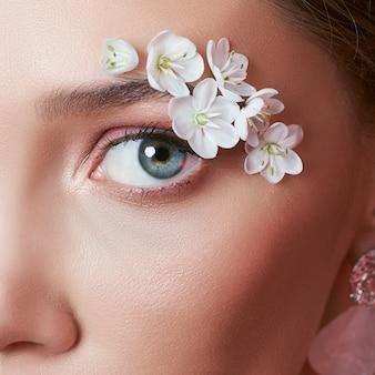Lente make-up oog vrouw met witte bloemen.