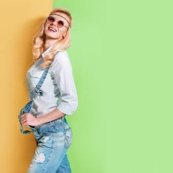 Lente meisje in modieuze zonnebril op een felle kleur achtergrond