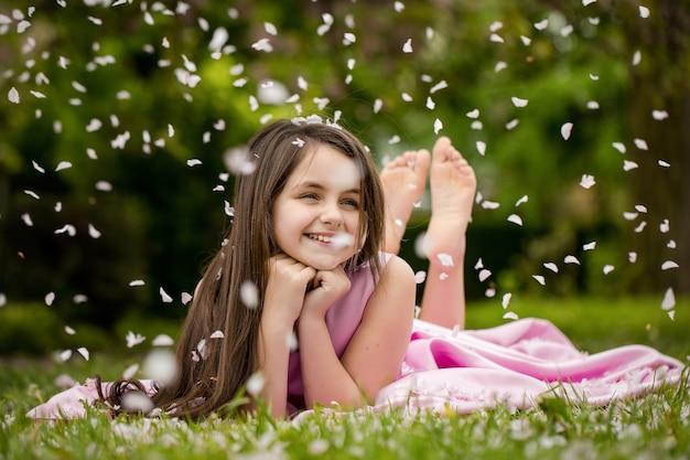 Lente meisje mooi meisje in roze jurk met lachend gezicht liggend op blote voeten op groen gras in de lente bloesem bloemblaadjes buiten