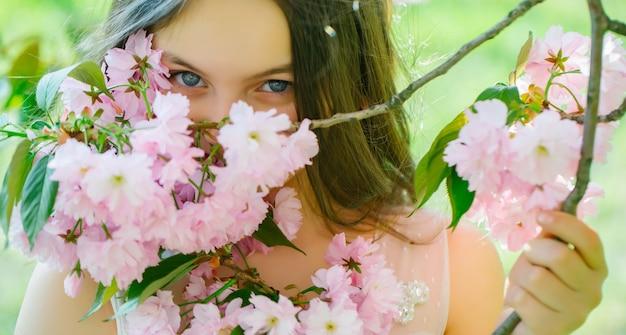 Lente meisje mooi tienermeisje met donkerbruin haar en lachend gezicht in de lente roze bloem bloesem zonnige dag close-up