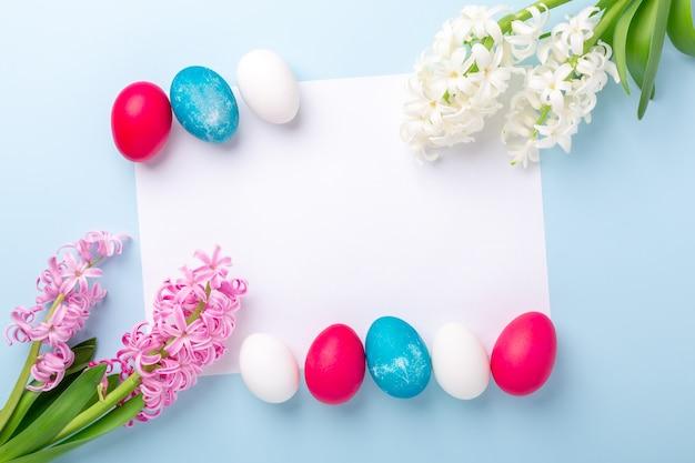 Lente mockup met paaseieren, hyacinten en blanco wit papier op blauwe achtergrond. pasen concept. kopieer ruimte. bovenaanzicht - afbeelding