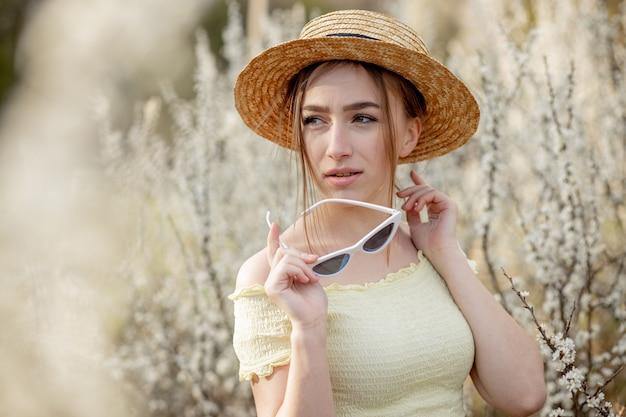 Lente mode meisje buiten portret in bloei. schoonheid romantische vrouw in bloemen. mooie vrouw die van aard geniet.