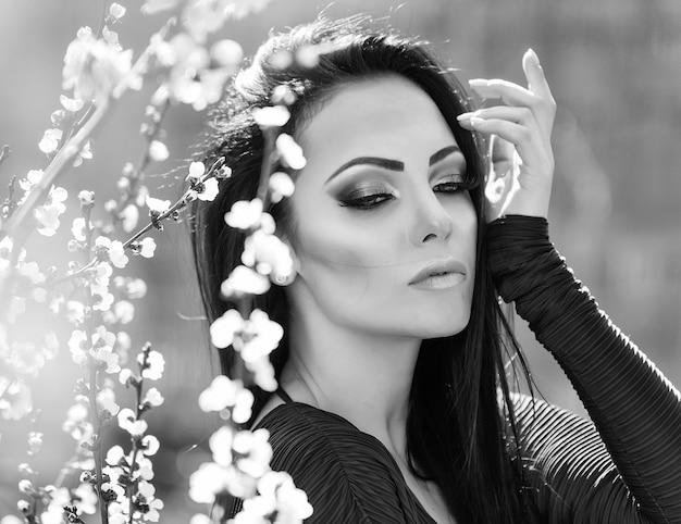 Lente mode vrouw buitenshuis portret in bloeiende bomen. schoonheid romantische vrouw in bloemen. sensuele dame. mooie vrouw die van aard geniet. romantische schoonheid.