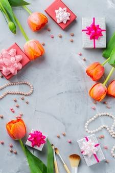 Lente mode vrouw meisje achtergrond met oranje kleurrijke tulpen, accessoires, geschenkdoos, make-up, sieraden. stijlvolle vrouwelijke flatlay kopie ruimte afbeelding