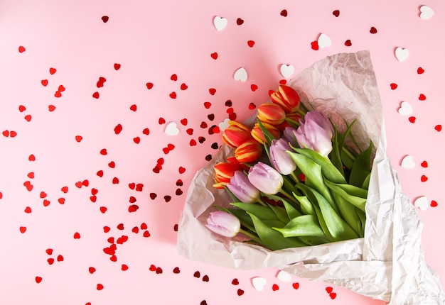 Lente mooie tulp bloemen op zachte pastel roze achtergrond met rood hart klatergoud. moederdag, wenskaart feestelijke decoratieve bloemensamenstelling.