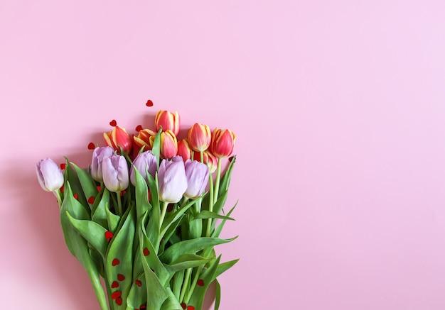 Lente mooie tulp bloemen op zachte pastel roze achtergrond. moederdag, wenskaart feestelijke decoratieve bloemensamenstelling.