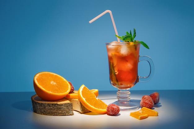 Lente oranje cocktail met bevroren aardbeien en munt.