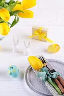Lente pasen achtergrond voor menu. paaseidecoratie, konijntje, linnenservet op plaat en keukenbestek op witte houten lijst.