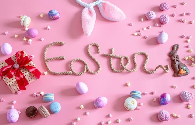 Lente pasen feestelijk. creatieve inscriptie pasen op roze met items van pasen decor.