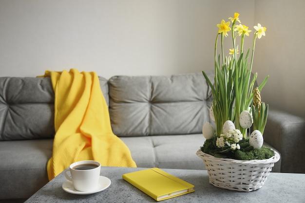 Lente pasen interieur in woonkamer met kopje koffie, pled en notitieboekje in trendy kleuren grijs en geel.