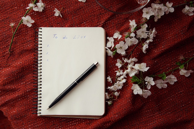 Lente plat lag bovenaanzicht thuiskantoor werkruimte - notitieboekje met theekop en kersenbloesemtakken op een rode bureauachtergrond