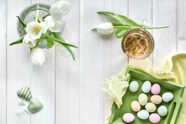 Lente plat lag in pastel kleuren, witte tulpen, kopje groene thee en suiker paaseieren op licht hout
