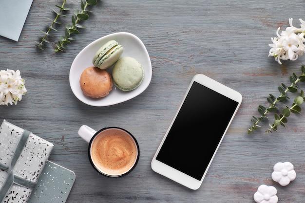 Lente plat met parelhyacint bloemen, eucalyptus, mobiele telefoon en kaarten