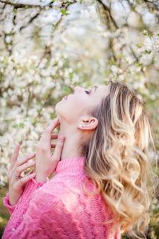 Lente portret van een jonge blonde in de buurt van een bloeiende boom. gelukkige jonge vrouw. voorjaar.