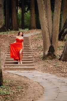 Lente portret van een lachend meisje in een lange rode jurk met lang haar wandelen in het park in het bos