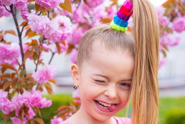 Lente portretten prachtige meisje op kersenbloesem achtergrond. knipogen op de camera. de lente