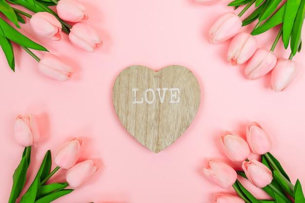 Lente roze tulpen en een houten valentijn in de vorm van een hart, op een roze achtergrond