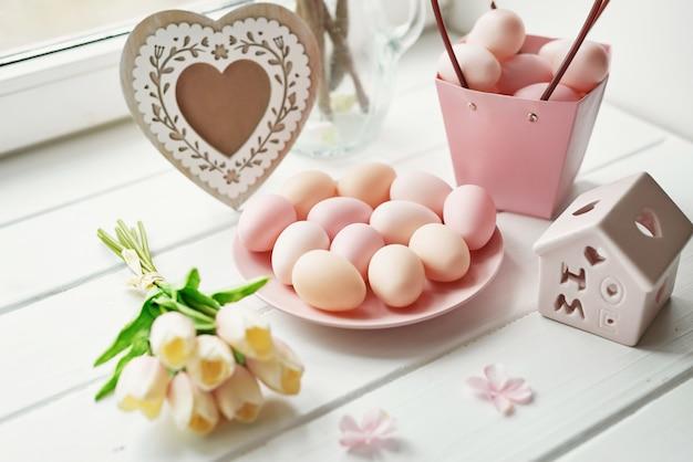 Lente samenstelling met gele tulp bloemen, roze eieren, hartvormige frame en kleine houten huis